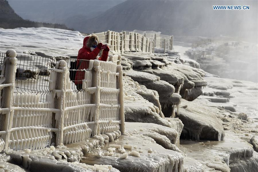 A visitor takes photos of icicles at the Hukou Waterfall scenic spot of the Yellow River at the border area between north China\'s Shanxi Province and northwest China\'s Shaanxi Province on Dec. 7, 2018. (Xinhua/Lyu Guiming)