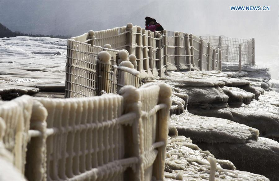 Visitors take photos of icicles at the Hukou Waterfall scenic spot of the Yellow River at the border area between north China\'s Shanxi Province and northwest China\'s Shaanxi Province on Dec. 7, 2018. (Xinhua/Lyu Guiming)