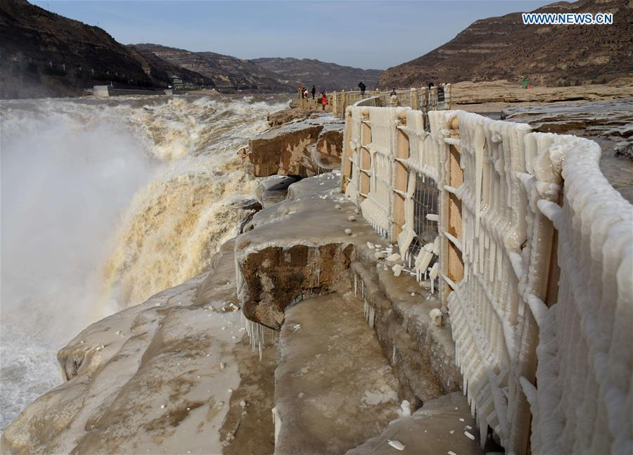 People visit the Hukou Waterfall scenic spot of the Yellow River at the border area between north China\'s Shanxi Province and northwest China\'s Shaanxi Province on Dec. 7, 2018. (Xinhua/Lyu Guiming)