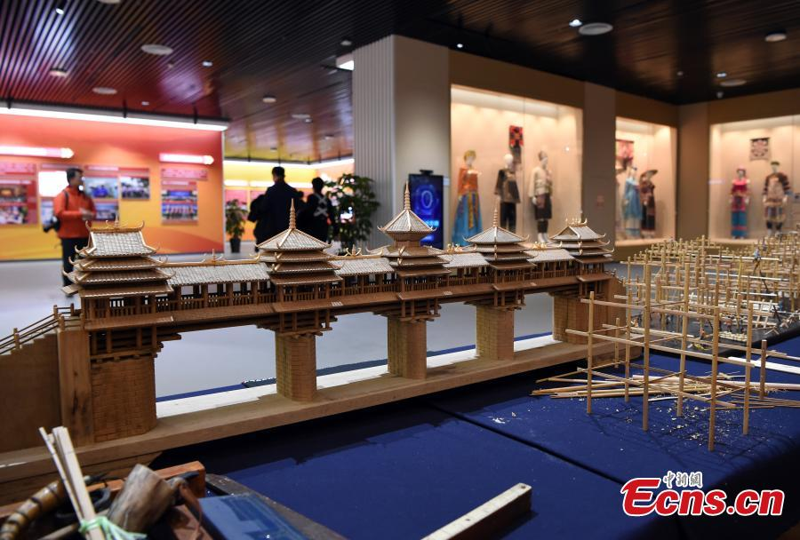 Visitors look at a model of Fengyu Bridge, or Wind and Rain Bridge because the pavilions built on the bridge provide shelter to people from the wind and rain, at an exhibition to mark the 60th anniversary of the establishment of the Guangxi Zhuang Autonomous Region in the region's capital Nanning City, Dec. 10, 2018. Established in 1958 as an autonomous region, Guangxi has a population of 56 million, including more than 20 million who identify as ethnic minorities. It tops in China's provincial-level regions in minority populations. (Photo: China News Service/Hou Yu)