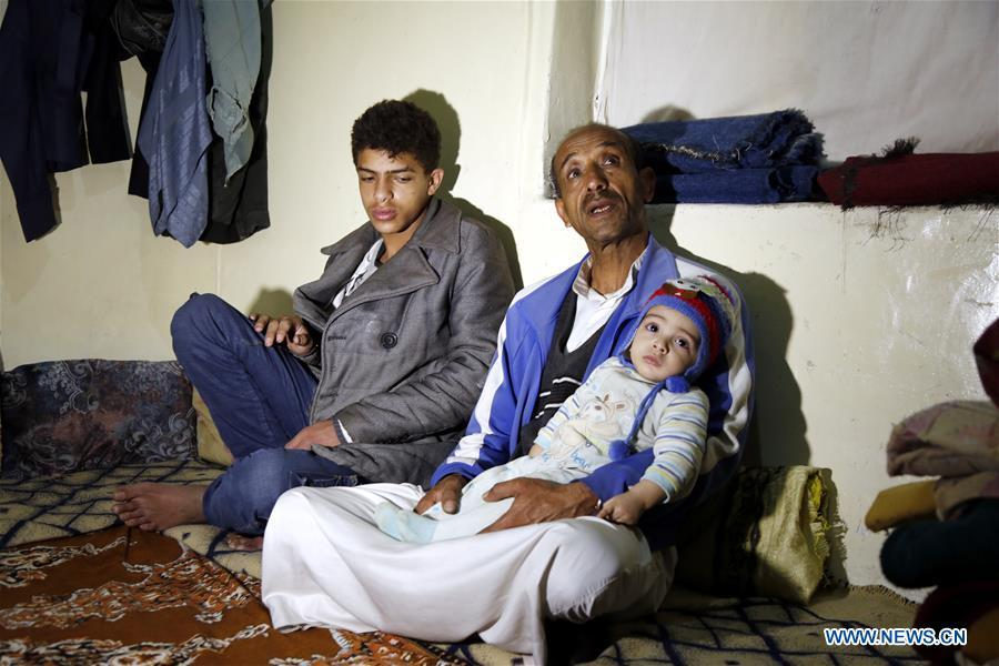 Ahmed al-Sharafi (C) holding his seven-month-old child Omar sits with his son Rami, 16, inside his house in Sanaa, Yemen, on Dec. 9, 2018. An estimated 85,000 children under the age of five may have died from extreme hunger between April 2015 and October 2018, according to the latest data released by Save the Children, an international organization for children\'s rights. (Xinhua/Mohammed Mohammed)