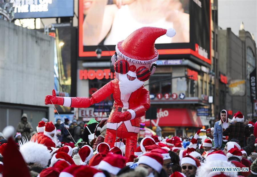 An inflatable Santa Claus is seen during the 2018 SantaCon in New York, the United States, Dec. 8, 2018. Dressed as Santa Claus or in festive costumes, hundreds of People participated in the 2018 SantaCon on Saturday, enjoying the Christmas atmosphere and raising money for charity. (Xinhua/Wang Ying)