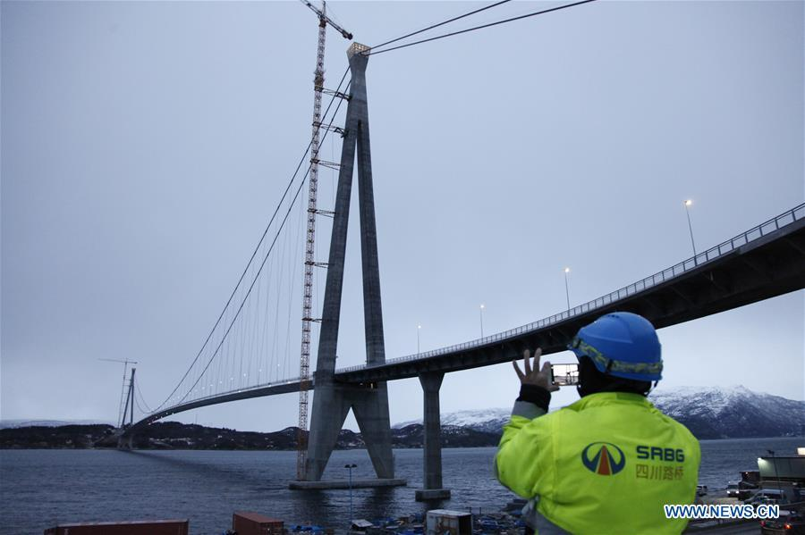 A Chinese worker takes photos of the Halogaland Bridge near Norway\'s northern port city of Narvik, Dec. 9, 2018. A ceremony was held Sunday to officially open Norway\'s second largest bridge that has been built by a Chinese company and its partners some 220 km inside the Arctic Circle. With a total length of 1,533 meters and a free span of 1,145 meters, the Halogaland Bridge near Norway\'s northern port city of Narvik is the longest suspension bridge within the Arctic Circle. (Xinhua/Liang Youchang)