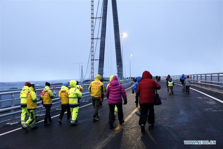Chinese workers and Norwegian citizens walk on the Halogaland Bridge near Norway\'s northern port city of Narvik, Dec. 9, 2018. A ceremony was held Sunday to officially open Norway\'s second largest bridge that has been built by a Chinese company and its partners some 220 km inside the Arctic Circle. With a total length of 1,533 meters and a free span of 1,145 meters, the Halogaland Bridge near Norway\'s northern port city of Narvik is the longest suspension bridge within the Arctic Circle. (Xinhua/Liang Youchang)
