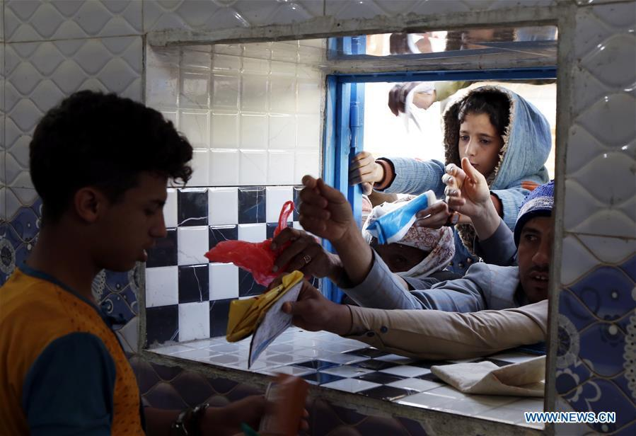 Yemeni people gather in front of a window of a charity center to receive food aid in Sanaa, Yemen, on Dec. 9, 2018. An estimated 85,000 children under the age of five may have died from extreme hunger between April 2015 and October 2018, according to the latest data released by Save the Children, an international organization for children\'s rights. (Xinhua/Mohammed Mohammed)