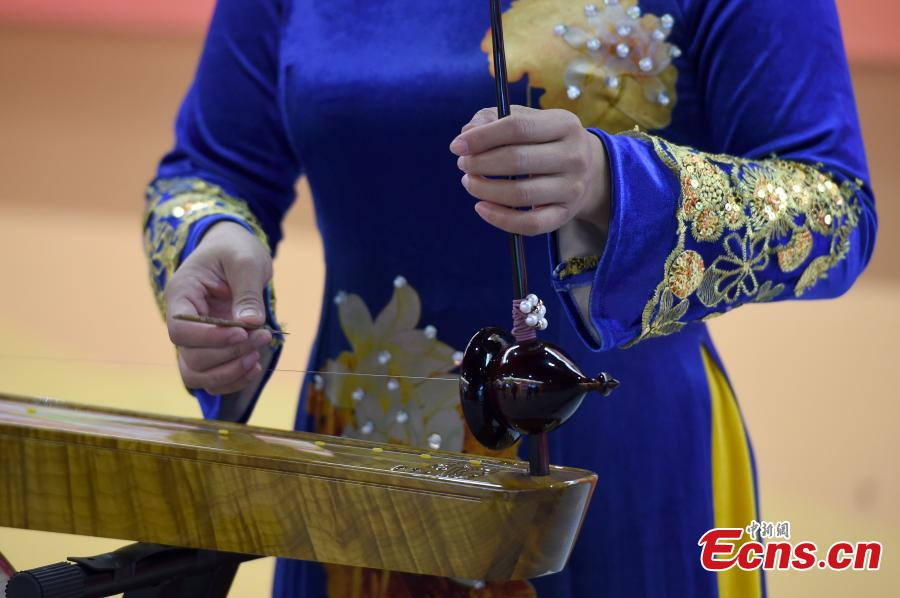 A woman from the Jing people plays a musical instrument at an exhibition to mark the 60th anniversary of the establishment of the Guangxi Zhuang Autonomous Region in the region's capital Nanning City, Dec. 10, 2018. Established in 1958 as an autonomous region, Guangxi has a population of 56 million, including more than 20 million who identify as ethnic minorities. It tops in China's provincial-level regions in minority populations. (Photo: China News Service/Hou Yu)