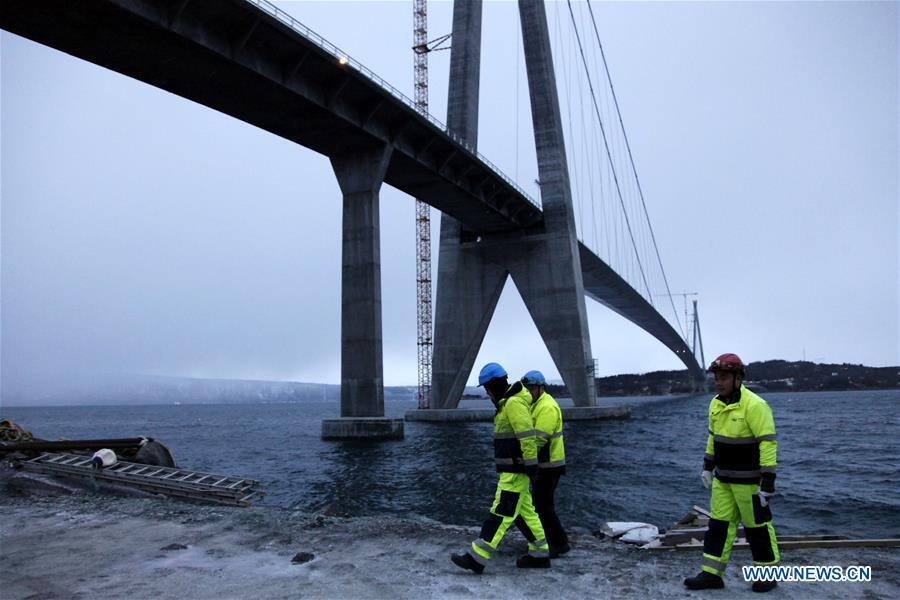 Chinese workers walk beneath the Halogaland Bridge near Norway\'s northern port city of Narvik, Dec. 9, 2018. A ceremony was held Sunday to officially open Norway\'s second largest bridge that has been built by a Chinese company and its partners some 220 km inside the Arctic Circle. With a total length of 1,533 meters and a free span of 1,145 meters, the Halogaland Bridge near Norway\'s northern port city of Narvik is the longest suspension bridge within the Arctic Circle. (Xinhua/Liang Youchang)