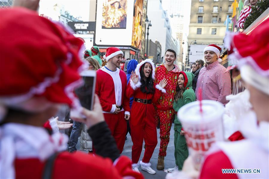 Revelers pose for photos during the 2018 SantaCon in New York, the United States, Dec. 8, 2018. Dressed as Santa Claus or in festive costumes, hundreds of People participated in the 2018 SantaCon on Saturday, enjoying the Christmas atmosphere and raising money for charity. (Xinhua/Wang Ying)