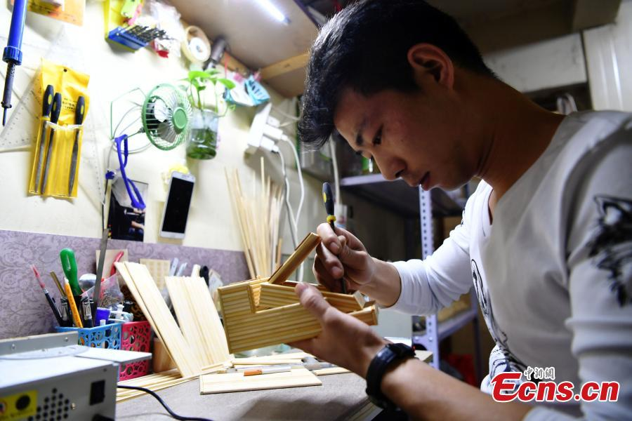 Xu Ruibin works with bamboo skewers for a creation at his wonton restaurant in Shijiazhuang City, Hebei Province, Dec. 10, 2018. Xu said he taught himself the handicraft in three months and is now able to make various designs. In the past two years, he has created over 300 works, including landmark buildings and elaborate villa miniatures. (Photo: China News Service/Zhai Yujia)