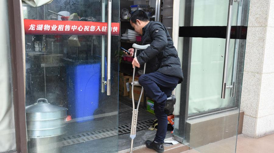 Chen Dengchao, 29, a delivery man in southwestern China\'s Chongqing city, waits for his delivery parcels at a restaurant. (Photo by Li Jiaqi for chinadaily.com.cn)   \
