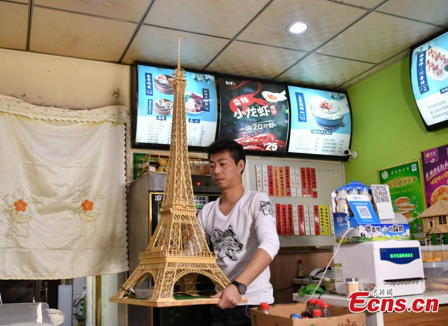 Xu Ruibin shows a replica of the Eiffel Tower made using bamboo skewers in two months at his wonton restaurant in Shijiazhuang City, Hebei Province, Dec. 10, 2018. Xu said he taught himself the handicraft in three months and is now able to make various designs. In the past two years, he has created over 300 works, including landmark buildings and elaborate villa miniatures. (Photo: China News Service/Zhai Yujia)