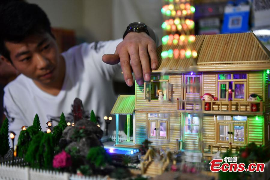 Xu Ruibin shows the openable window on a building made using bamboo skewers at his wonton restaurant in Shijiazhuang City, Hebei Province, Dec. 10, 2018. Xu said he taught himself the handicraft in three months and is now able to make various designs. In the past two years, he has created over 300 works, including landmark buildings and elaborate villa miniatures. (Photo: China News Service/Zhai Yujia)