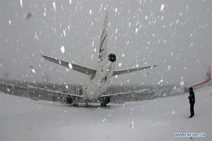 A staff worker checks an aircraft in snow at Yantai Penglai International Airport in Yantai City, east China\'s Shandong Province, Dec. 11, 2018. Parts of Shandong Province met snow on Tuesday. (Xinhua/Tang Ke)