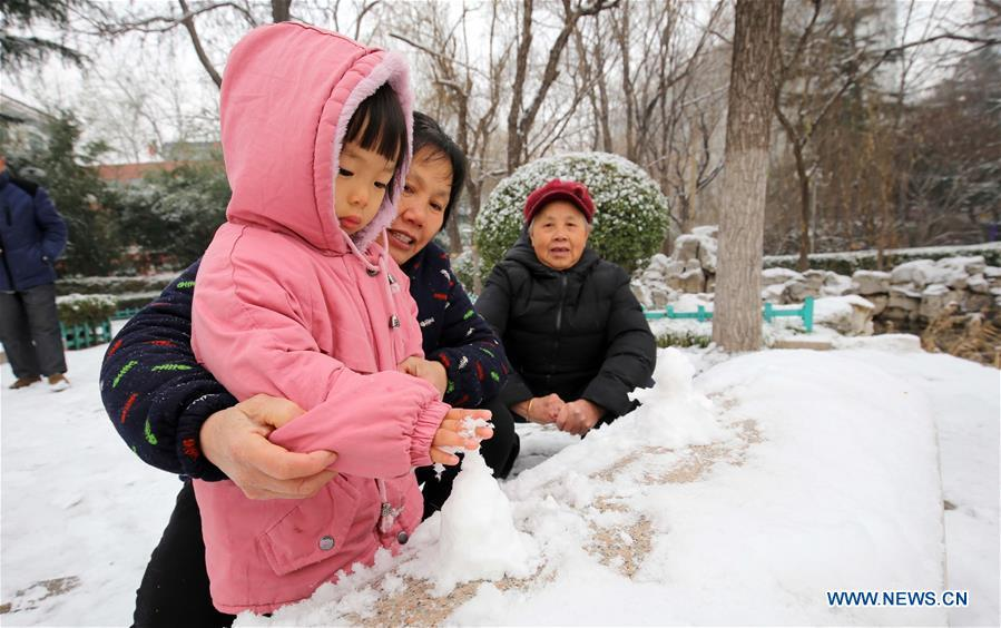 A child makes a snow cone in Weifang City, east China\'s Shandong Province, Dec. 11, 2018. Parts of Shandong Province met snow on Tuesday. (Xinhua/Zhang Chi)