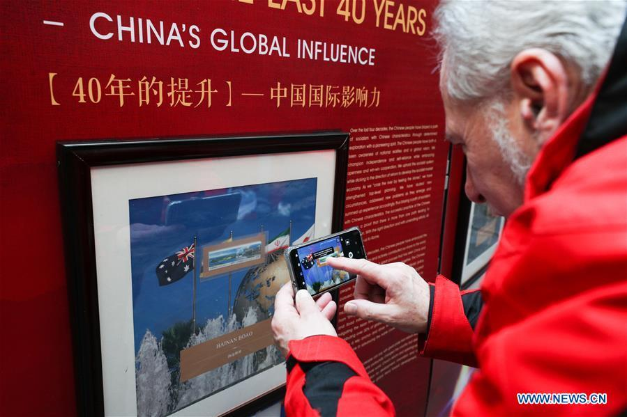 A visitor takes photos of the stamps showing China\'s global influence during the \