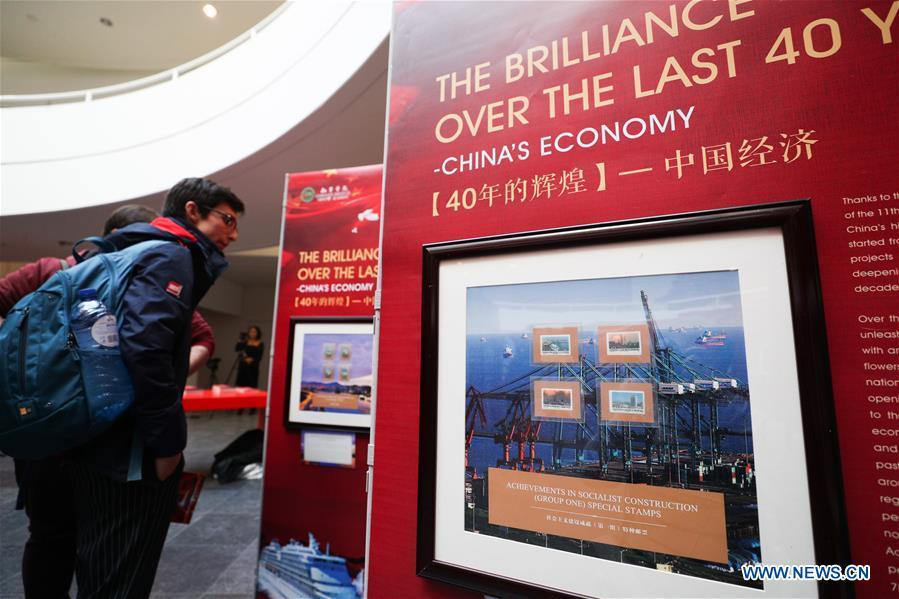 Visitors watch the stamps showing China\'s economic achievements during the \