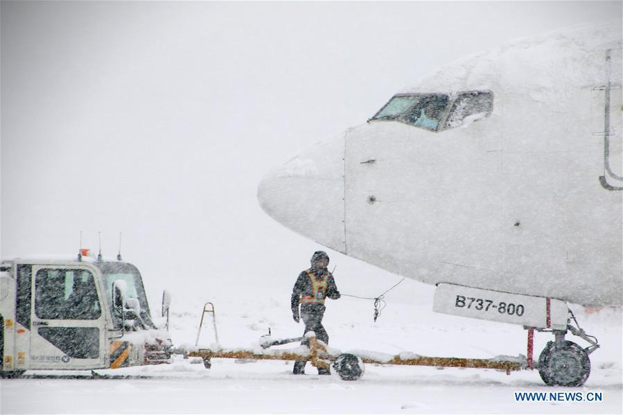 A tractor tows an aircraft in snow at Yantai Penglai International Airport in Yantai City, east China\'s Shandong Province, Dec. 11, 2018. Parts of Shandong Province met snow on Tuesday. (Xinhua/Tang Ke)