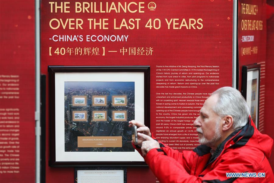 A visitor takes photos of the stamps showing China\'s economic achievements during the \