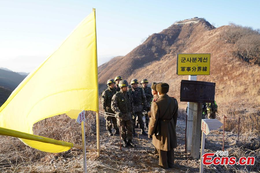 In this photo provided by South Korea Defense Ministry, South Korean army soldiers, wearing helmets, prepare to cross the Military Demarcation Line as North Korean army soldiers stand inside the Demilitarized Zone (DMZ) to inspect the dismantled North Korean guard post in the central section of the inter-Korean border in Cheorwon, Dec. 12, 2018. Dozens of soldiers from two countries crossed over the world\'s most heavily armed border Wednesday as they inspected the sites of their rival\'s front-line guard posts to verify they\'d been removed. (Photo provided by South Korea Defense Ministry)