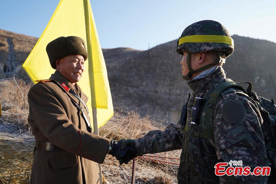 In this photo provided by South Korea Defense Ministry, South Korean army Col. Yun Myung-shick (right) shakes hands with North Korean army Lt. Col. Ri Jong Su before crossing the Military Demarcation Line inside the Demilitarized Zone (DMZ) to inspect the dismantled North Korean guard post in the central section of the inter-Korean border in Cheorwon, Dec. 12, 2018. Dozens of soldiers from two countries crossed over the world\'s most heavily armed border Wednesday as they inspected the sites of their rival\'s front-line guard posts to verify they\'d been removed. (Photo provided by South Korea Defense Ministry)