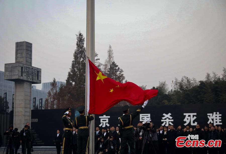 A national flag is flown at half-mast Thursday morning at the Memorial Hall for the Victims of the Nanjing Massacre, Dec. 13, 2018. On Thursday, China marked the fifth national memorial day to commemorate the victims of the Nanjing Massacre, in which Japanese invaders slaughtered about 300,000 Chinese during a six-week rampage after they captured the city, then China\'s capital, in 1937. In front of the darkly-dressed crowd at the ceremony, China\'s national flag is flown at half-mast. In February 2014, China\'s top legislature designated December 13 as the National Memorial Day for Nanjing Massacre Victims. (Photo: China News Service/Yang Bo)