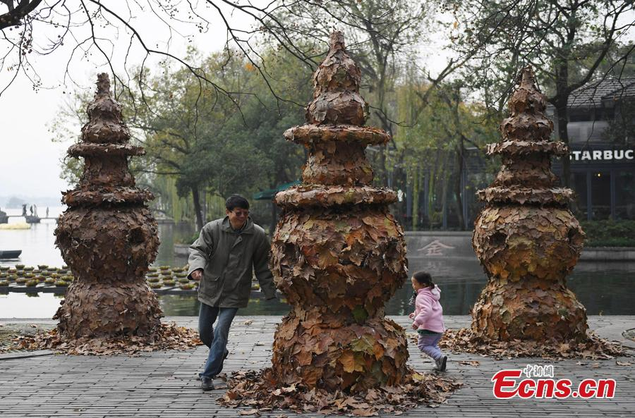 People play around a foliage artwork at the West Lake in Hangzhou, Zhejiang Province, Dec. 12, 2108. Hosted by China Academy of Art, the Foliage Artwork Festival attracted many visitors. (Photo: China News Service/Wang Gang)