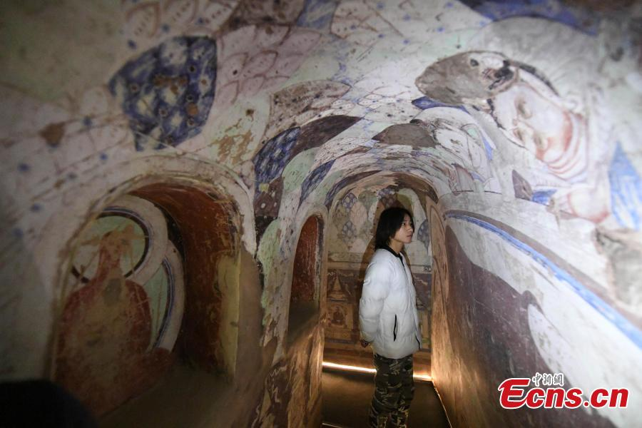 A visitor inside a life-size replica of a cave from the Kizil Caves in Northwest China's Xinjiang Uygur Autonomous Region during an exhibition at Lanzhou University's Yuzhong campus in Yuzhong County, Northwest China's Gansu Province, December 13, 2018. Included in the exhibition were images of 137 murals, which were originally from the Kizil Caves but are now kept overseas, two replicas of original caves, and four digital caves. (Photo: China News Service/Yang Yanmin)