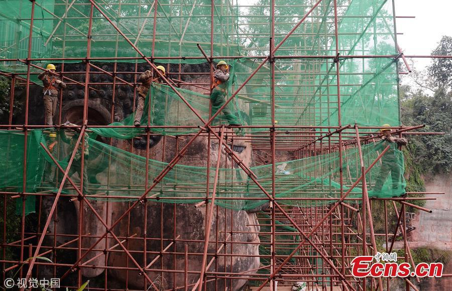 A 71-meter-tall Buddha statue-enclosed by scaffolding in the Leshan Giant Buddha Scenic Zone in Leshan, Sichuan province-has been undergoing repairs and maintenance since Oct 8. The price of entrance tickets to the scenic zone were cut by half on Monday because of the work, according to its administrative committee.(Photo/VCG)
