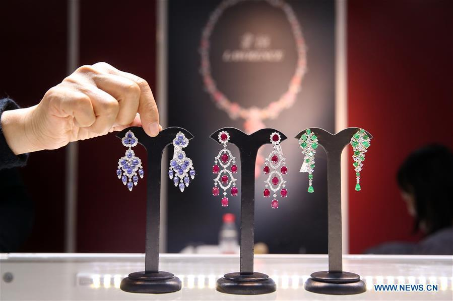 A staff worker arranges exhibits at the 2018 China International Jewelry Fair in Beijing, capital of China, Dec. 13, 2018. Exhibitors from 23 countries and regions attended the fair, opened on Thursday. (Xinhua/Chen Xiaogen)