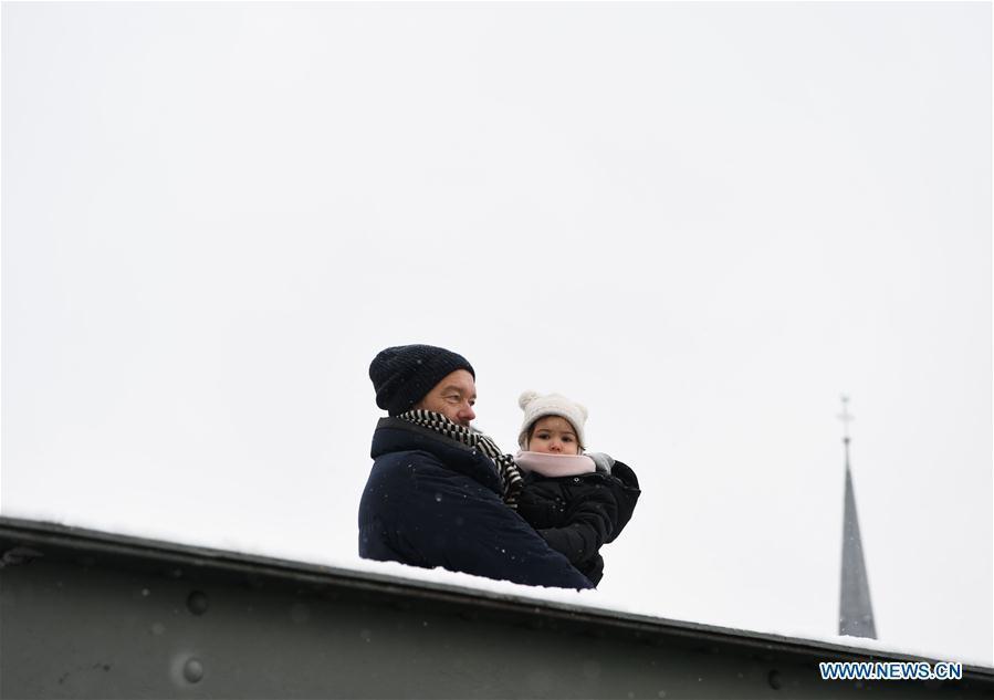 A man with a child stands on the Eiserner Steg footbridge amid snow in Frankfurt, Germany, on Dec. 16, 2018. A snowfall hit Frankfurt on Sunday. (Xinhua/Lu Yang)
