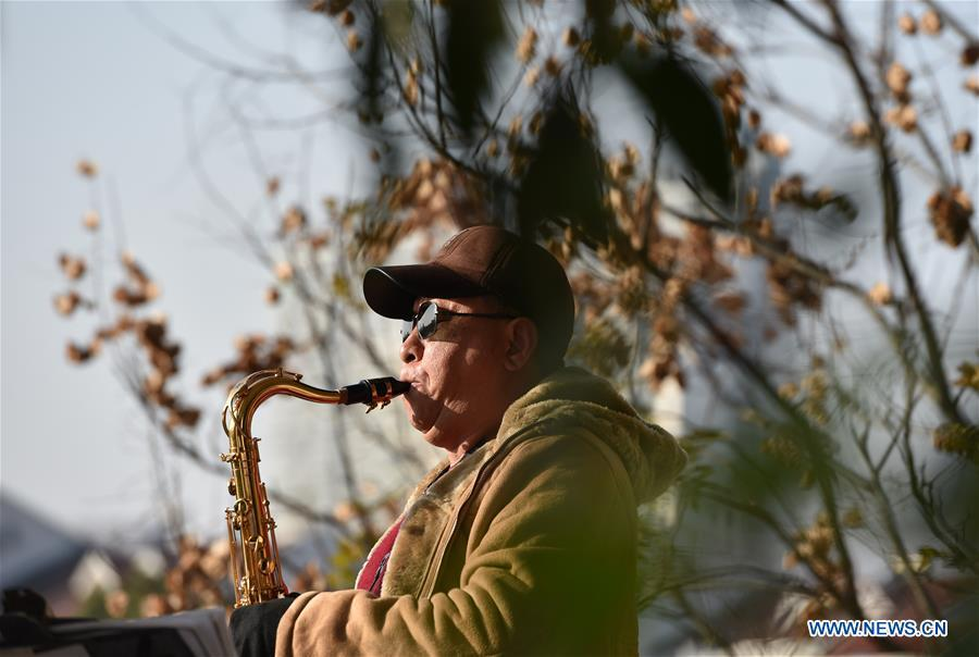 A man plays the saxophone at Huancheng Park in Hefei, capital of east China\'s Anhui Province, Dec. 16, 2018. Balmy weather in winter in Hefei recently helped promote outdoor recreation. (Xinhua/Yang Xiaoyuan)