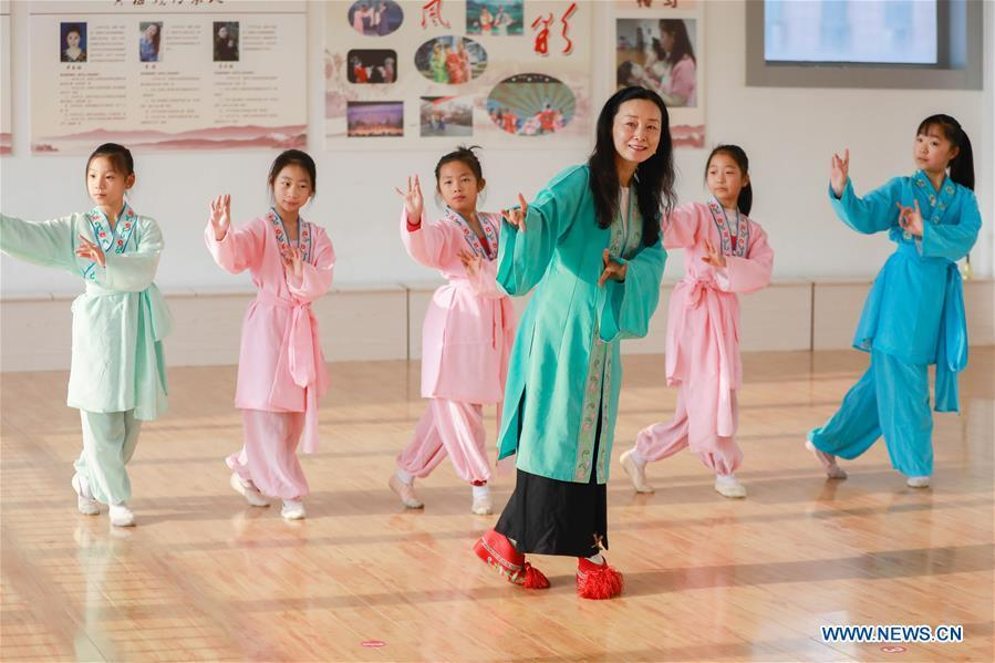 Meng Qingmei (3rd R), a performer of Xuyi Huangmei Opera Troupe, teaches students Huangmei Opera, in Xuyi County of east China\'s Jiangsu Province, Dec. 16, 2018. Performers of the troupe have been teaching local students Huangmei Opera in recent years to promote the traditional opera. (Xinhua/Zhou Haijun)