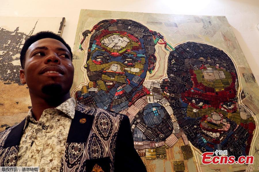 Desire Koffi, 24-year-old artist, poses next to his artwork during an exhibition in Abidjan, Ivory Coast, Dec. 1, 2018. Desire Koffi often walks through Koumassi, a popular district of Ivory Coast\'s main city Abidjan, to collect old mobile phones that he buys from people for 500 CFA francs ($0.8726) a pair. Back home, he dismantles the phones with a hammer to pull out the screens and keyboards. He uses them for his paintings. One can take him up to three or five days of work. (Photo/Agencies)