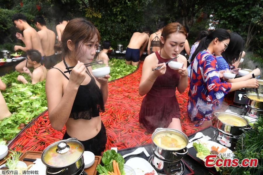A group of people enjoy hotpots while soaking in a hotpot-style hot spring in the city of Hangzhou in Zhejiang Province, December 16, 2018. The hot spring designed as \