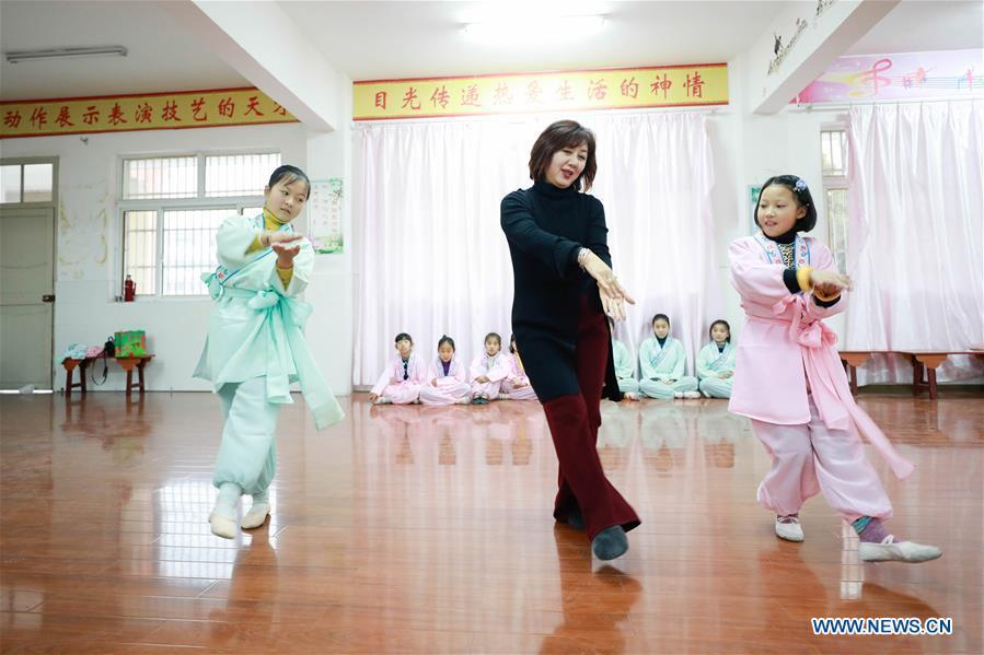 Bi Chunmei (C), a performer of Xuyi Huangmei Opera Troupe, teaches students Huangmei Opera at Wudun Primary School, in Xuyi County of east China\'s Jiangsu Province, Dec. 16, 2018. Performers of the troupe have been teaching local students Huangmei Opera in recent years to promote the traditional opera. (Xinhua/Zhou Haijun)