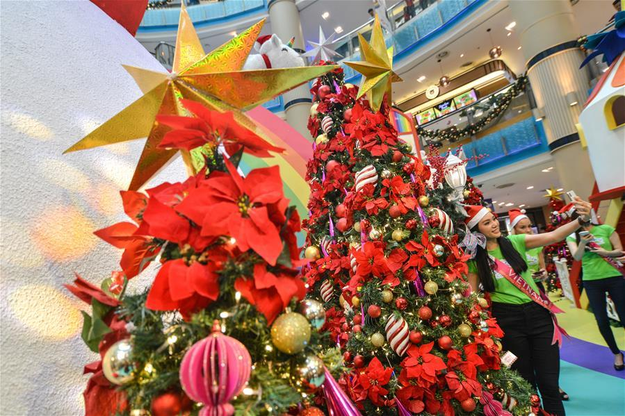 A woman takes selfies in front of Christmas trees in Kuala Lumpur, Malaysia, on Dec. 16, 2018. (Xinhua/Chong Voon Chung)