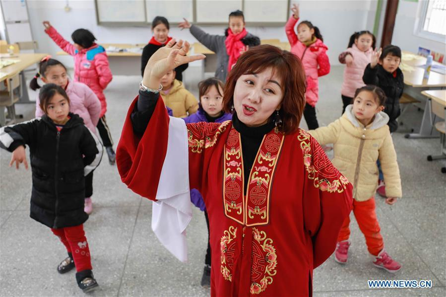 Bi Chunmei, a performer of Xuyi Huangmei Opera Troupe, teaches students Huangmei Opera at Gusang Primary School, in Xuyi County of east China\'s Jiangsu Province, Dec. 16, 2018. Performers of the troupe have been teaching local students Huangmei Opera in recent years to promote the traditional opera. (Xinhua/Zhou Haijun)