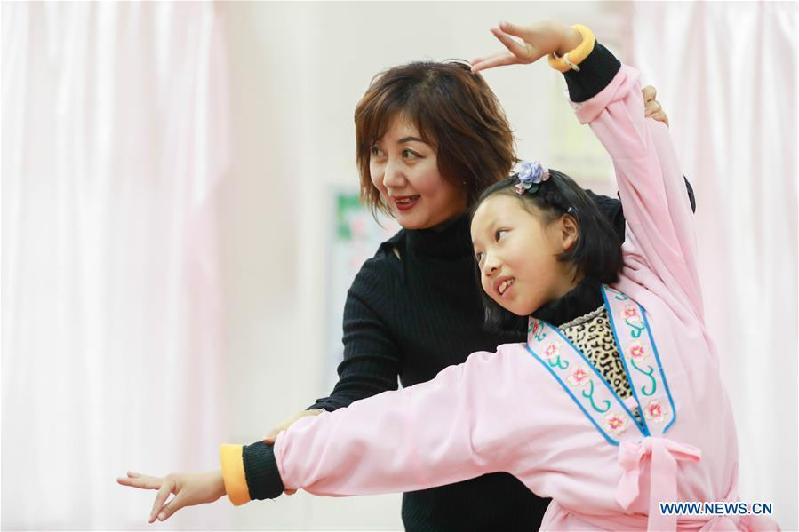 Bi Chunmei (L), a performer of Xuyi Huangmei Opera Troupe, teaches a student Huangmei Opera at Wudun Primary School, in Xuyi County of east China\'s Jiangsu Province, Dec. 16, 2018. Performers of the troupe have been teaching local students Huangmei Opera in recent years to promote the traditional opera. (Xinhua/Zhou Haijun)