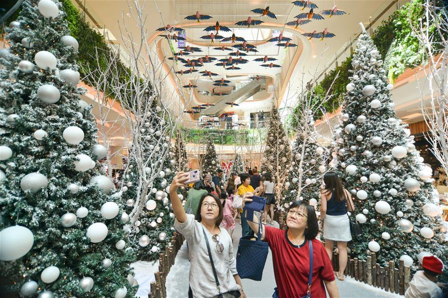 People pose for photos with Christmas decorations at a shopping mall in Kuala Lumpur, Malaysia, on Dec. 16, 2018. (Xinhua/Chong Voon Chung)