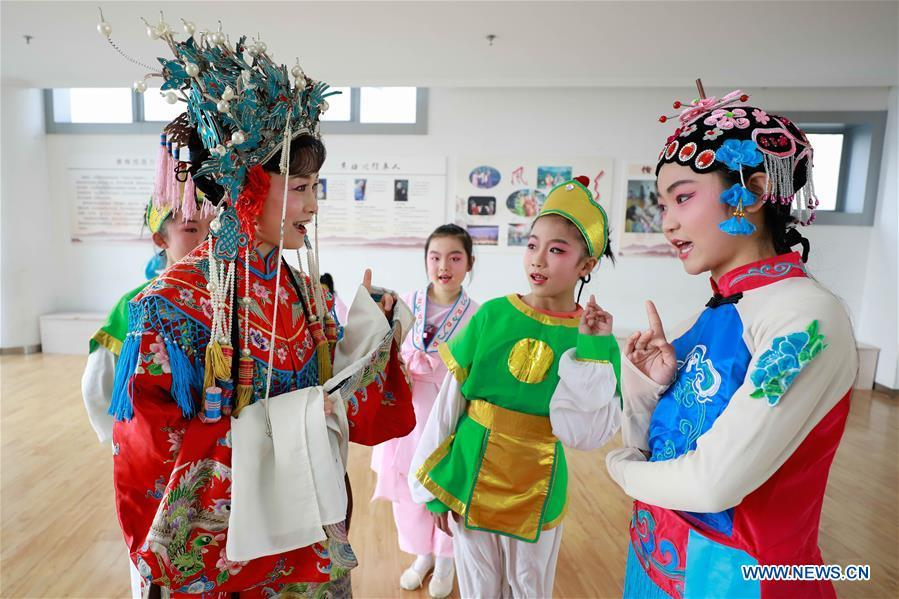 Meng Qingmei (L, front), a performer of Xuyi Huangmei Opera Troupe, teaches students Huangmei Opera, in Xuyi County of east China\'s Jiangsu Province, Dec. 16, 2018. Performers of the troupe have been teaching local students Huangmei Opera in recent years to promote the traditional opera. (Xinhua/Zhou Haijun)
