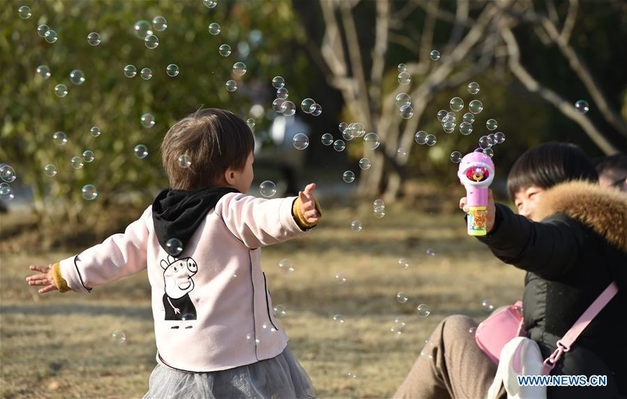 A kid plays with soap bubbles at Xinghua Park in Hefei, capital of east China\'s Anhui Province, Dec. 16, 2018. Balmy weather in winter in Hefei recently helped promote outdoor recreation. (Xinhua/Yang Xiaoyuan)