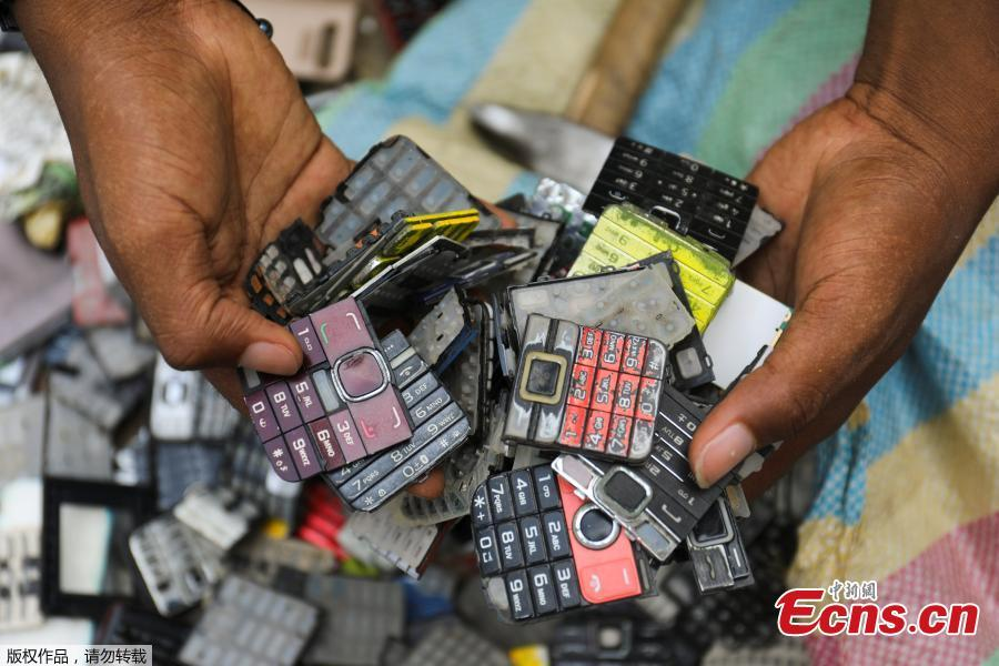 Desire Koffi, 24-year-old artist, holds discarded phone keyboards at his workshop in Abidjan, Ivory Coast Nov. 30, 2018. Desire Koffi often walks through Koumassi, a popular district of Ivory Coast\'s main city Abidjan, to collect old mobile phones that he buys from people for 500 CFA francs ($0.8726) a pair. Back home, he dismantles the phones with a hammer to pull out the screens and keyboards. He uses them for his paintings. One can take him up to three or five days of work. (Photo/Agencies)