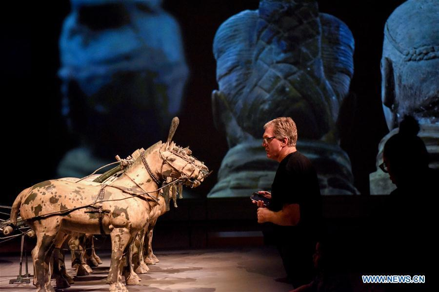 A visitor views the exhibits during the exhibition Terracotta Warriors: Guardians of Immortality at the National Museum of New Zealand in Wellington, New Zealand, on Dec. 15, 2018. The landmark exhibition of Terracotta Warriors: Guardians of Immortality opened to public on Saturday at the National Museum of New Zealand. The exhibition features eight warriors standing 180 cm tall, and two full-size horses from the famous terracotta army, as well as two half-size replica bronze horse-drawn chariots. Also on display are more than 160 exquisite works of ancient Chinese art made from gold, jade and bronze. \