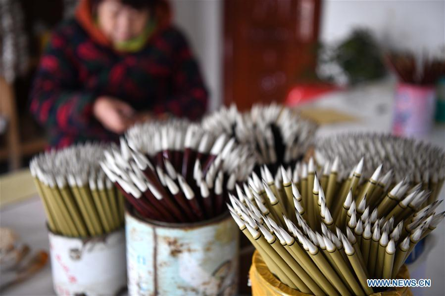 A worker sticks the trademarks on the Xuan ink brushes at a workshop in Huangcun Town of Jingxian County, east China\'s Anhui Province, Dec. 14, 2018. Huangcun Town has a long history of the Xuan ink brush making. The ink brush, ink, Chinese Xuan paper and ink slabs are four traditional writing materials of Chinese stationery. (Xinhua/Liu Junxi)