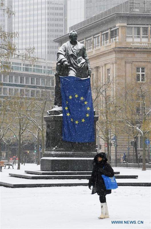 A woman walks past the snow-covered Goethe Plaza in Frankfurt, Germany, on Dec. 16, 2018. A snowfall hit Frankfurt on Sunday. (Xinhua/Lu Yang)