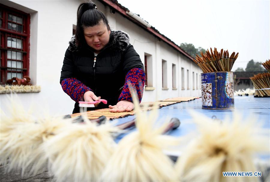 A worker dries the Xuan ink brushes at a workshop in Huangcun Town of Jingxian County, east China\'s Anhui Province, Dec. 14, 2018. Huangcun Town has a long history of the Xuan ink brush making. The ink brush, ink, Chinese Xuan paper and ink slabs are four traditional writing materials of Chinese stationery. (Xinhua/Liu Junxi)