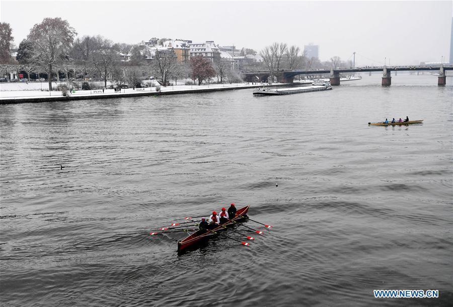People paddle along the Main River in Frankfurt, Germany, on Dec. 16, 2018. A snowfall hit Frankfurt on Sunday. (Xinhua/Lu Yang)