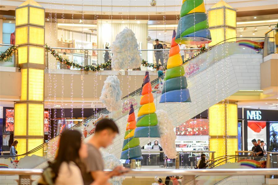 Customers walk past decorations set up for the upcoming Christmas season at a shopping mall in Kuala Lumpur, Malaysia, on Dec. 16, 2018. (Xinhua/Chong Voon Chung)