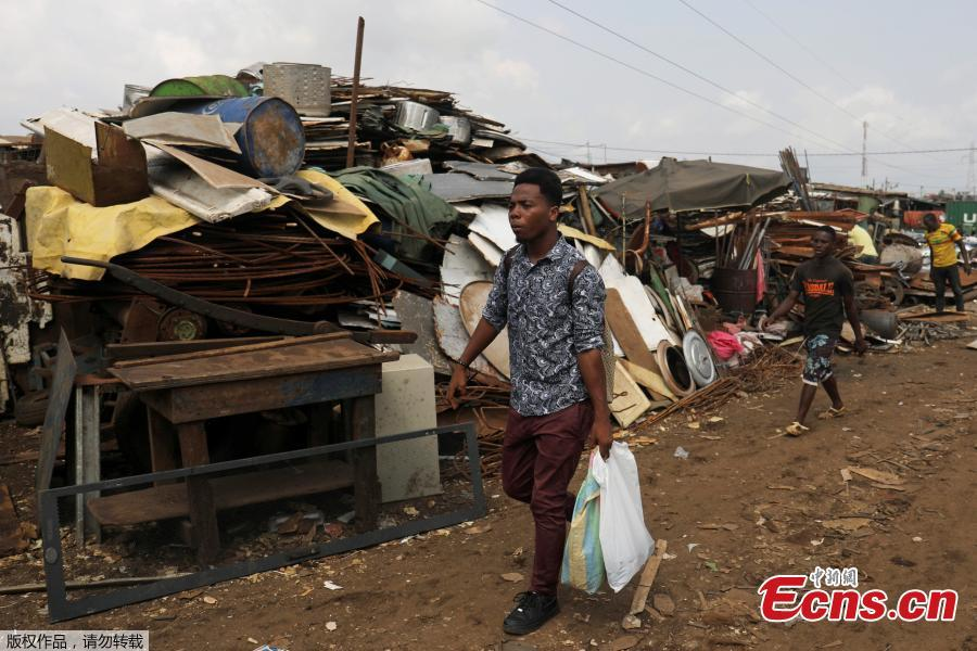 Desire Koffi, 24-year-old artist, walks at a recycling area in search of old mobile phones in Abidjan, Ivory Coast, Nov. 30, 2018. Desire Koffi often walks through Koumassi, a popular district of Ivory Coast\'s main city Abidjan, to collect old mobile phones that he buys from people for 500 CFA francs ($0.8726) a pair. Back home, he dismantles the phones with a hammer to pull out the screens and keyboards. He uses them for his paintings. One can take him up to three or five days of work. (Photo/Agencies)