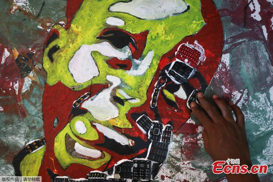 Desire Koffi, 24-year-old artist, places electronic waste on his painting at his workshop in Abidjan, Ivory Coast, Dec. 5, 2018. Desire Koffi often walks through Koumassi, a popular district of Ivory Coast\'s main city Abidjan, to collect old mobile phones that he buys from people for 500 CFA francs ($0.8726) a pair. Back home, he dismantles the phones with a hammer to pull out the screens and keyboards. He uses them for his paintings. One can take him up to three or five days of work. (Photo/Agencies)